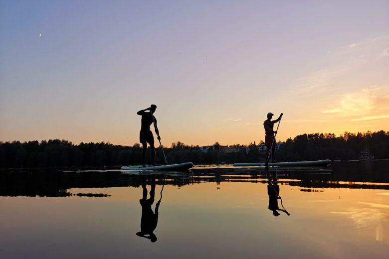 Varaston sup-laudoilla melomassa kaksi ihmistä järvellä