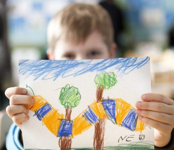 Pieni poika näyttää väriliiduilla piirtämäänsä maisemakuvaa katsojalle. Kuvassa on sininen taivas, vihreää ruohikkoa, kaksi puuta ja mato, jossa on oransseja ja sinisiä raitoja.