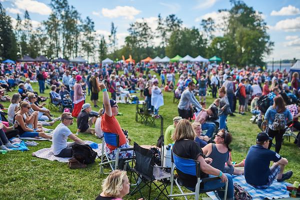 Ylisfestareiden yleisöä Pitkäniemen nurmialueella seisomassa, istumassa ja viettämässä piknikiä sekä seuraamassa festivaaliesiintyjiä lavalla.