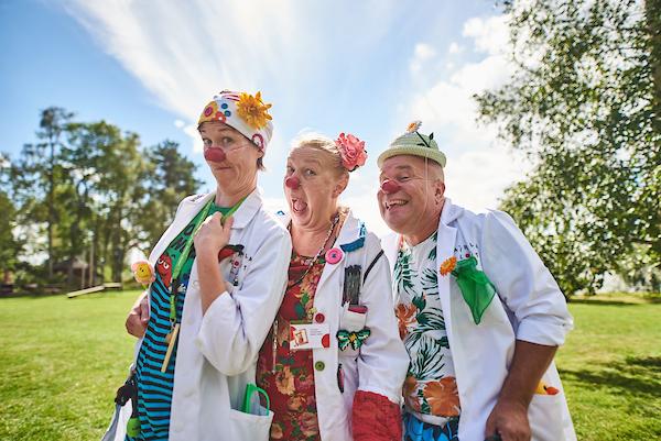 Ylisfestareilla vuonna 2018 esiintyneet kolme sairaalaklovnia. Klovneilla on punaiset irtonenät, valkoiset sairaalatakit sekä iloiset väriset hatut ja vaatteet.