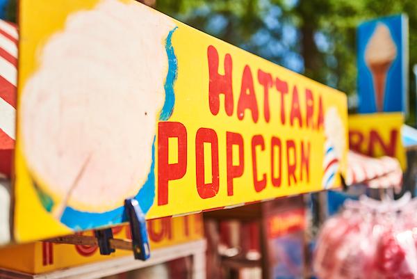 Hattaraa ja popcornia myyvän kojun värikäs mainoskyltti Ylisfestareiden ruokamaailman alueella.