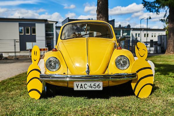 Kirkkaankeltainen kuplavolkkari vihreällä nurmella Ylisfestareilla. Auton kylkiin on kiinnitetty keltaiset mehiläiset, jotka ovat festivaalin tunnuksia.