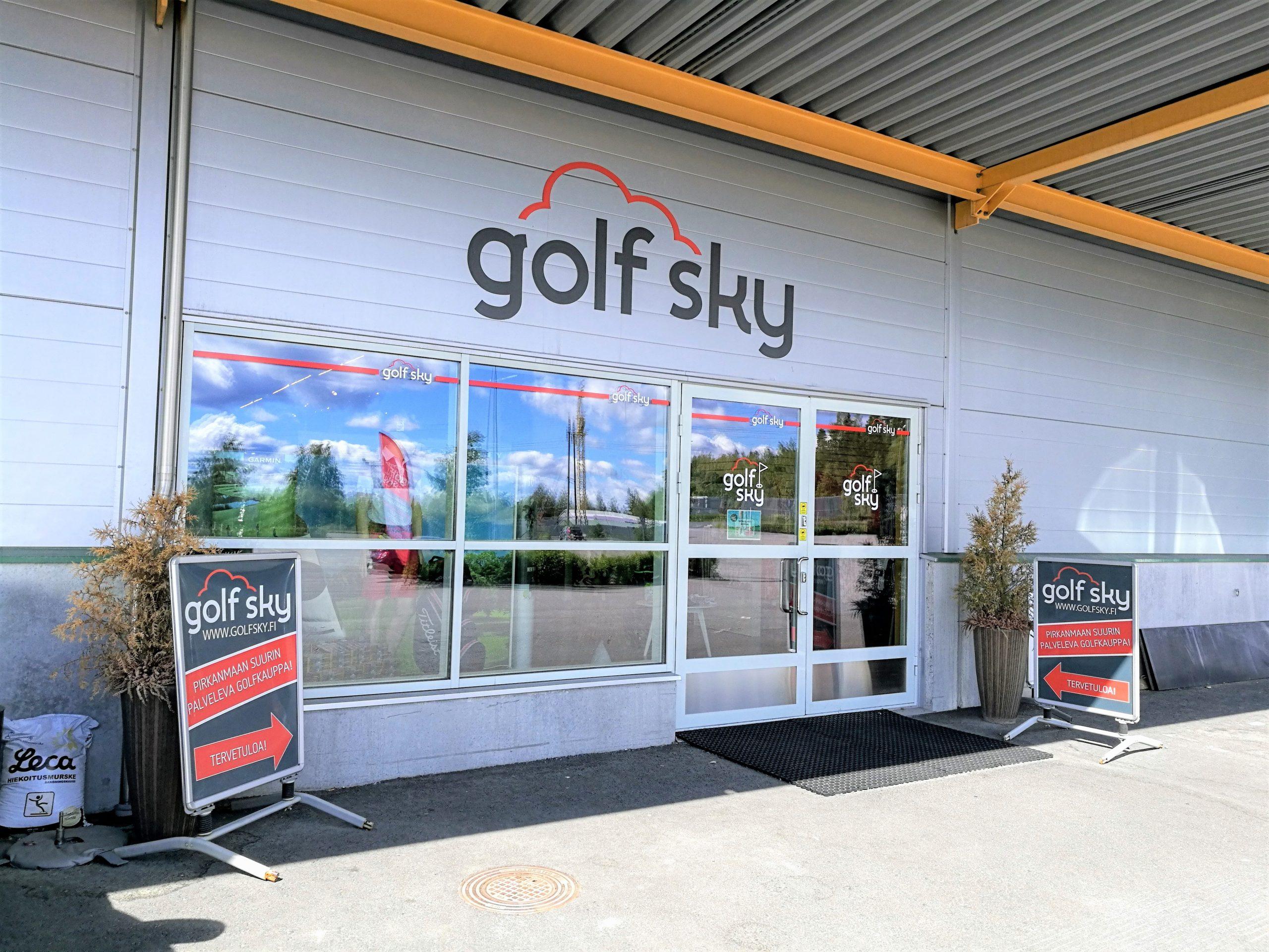 Golf Skyn harjoittelukeskuksen pääovi, jonka edessä yrityksen mainoskyltit.