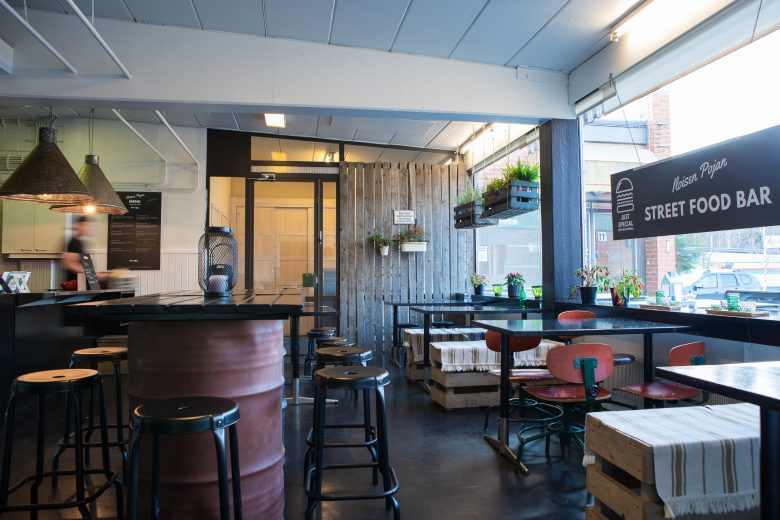 Sisäkuva Iloisen Pojan Street Food Barista, jossa vasemmalla tiski ja oikealla pöytiä ja tuoleja.