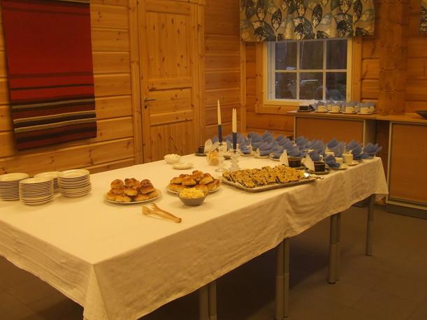 Juhava kahvipöytä tarjoiluineen ja kahvikuppeineen katettuna Jyräkallion majalla.