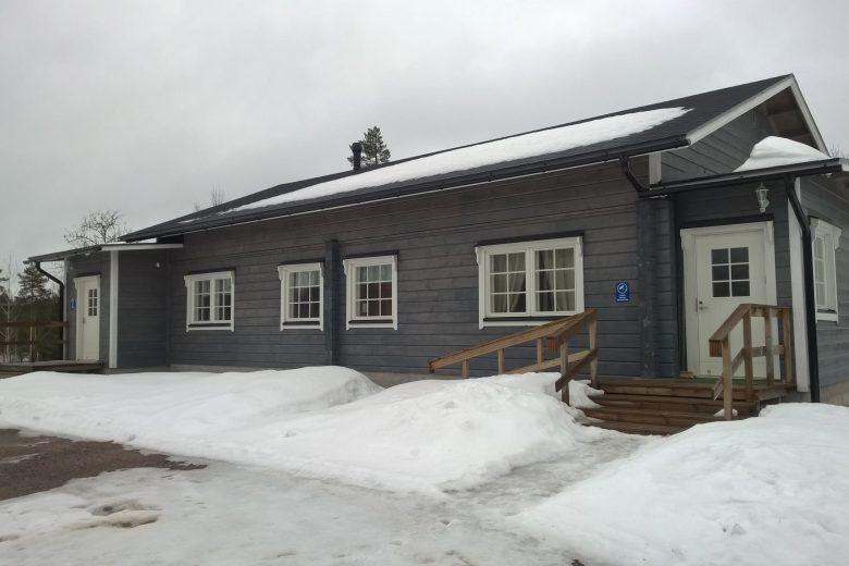 Jyräkallion maja on harmaa uudehko hirsirakennus, jossa on valkoiset ikkunanpuitteet ja ovi sekä rappuset ja pyörätuoliramppi.