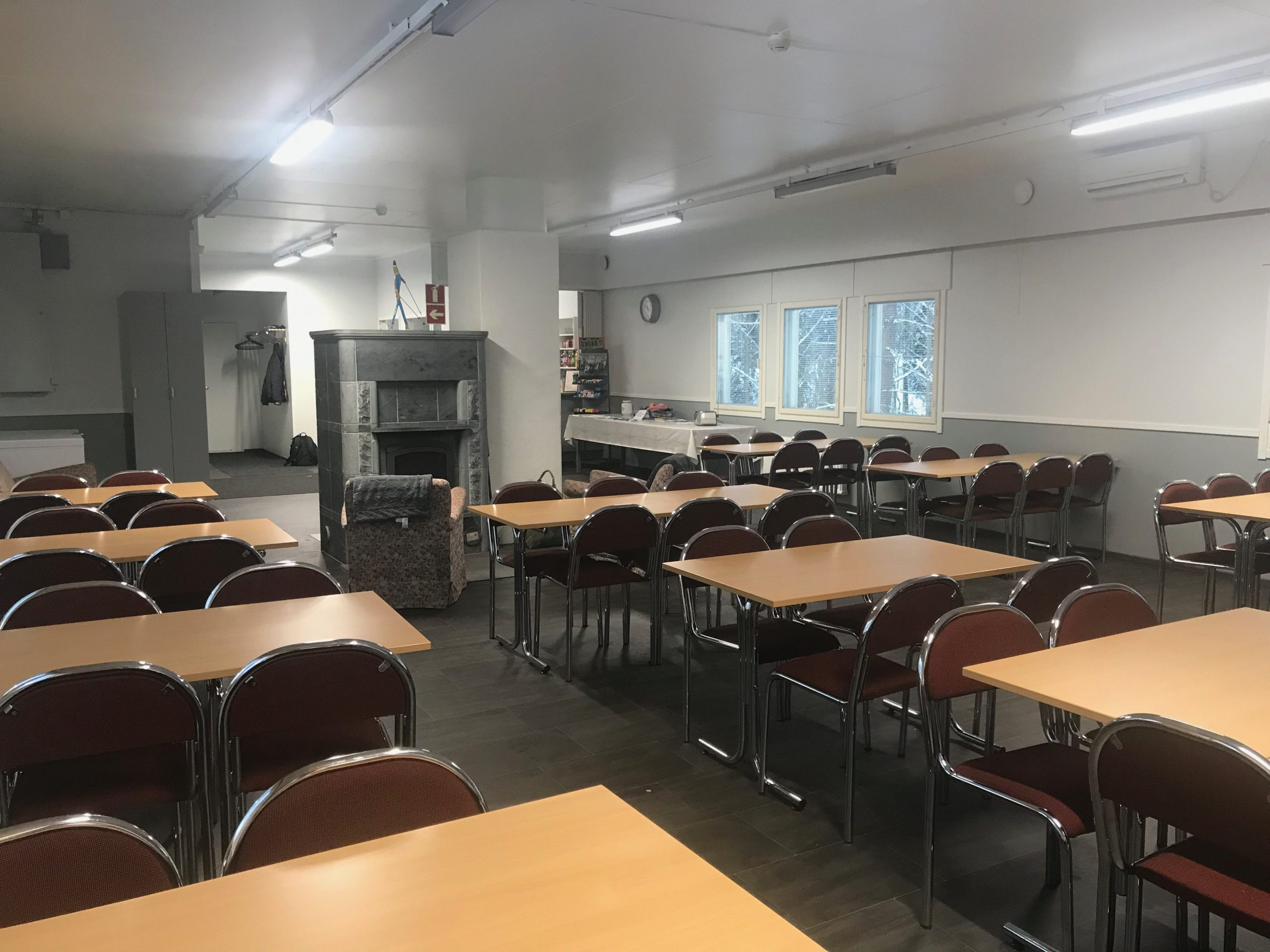 Koukkujärven majan kokoustilassa on useita pöytiä ja tuoleja sekä vuolukivitakka keskellä tilaa.