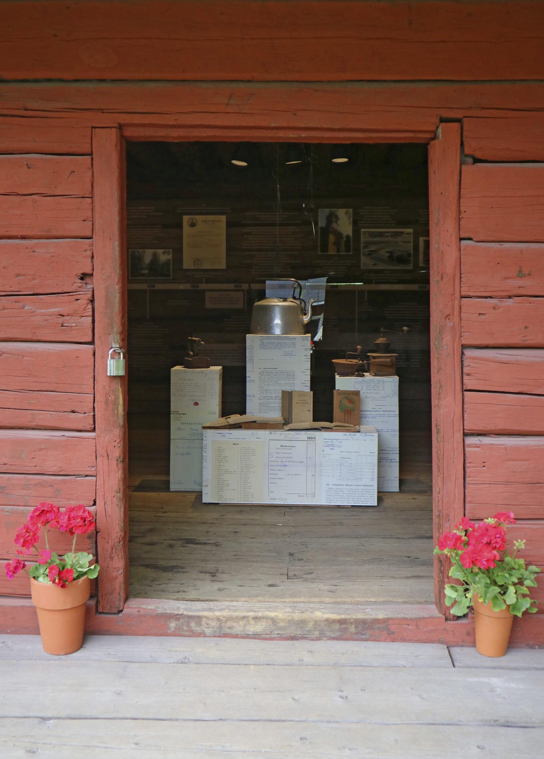 Hinttalan kotiseutumuseon punamullalla maalatun aitan ovi, joka on avoinna, Oviaukosta näkyy Luhti-näyttelyn vanhaa esineistöä, kuten kahvipannu, kahvimyllyjä ja vanha, rautainen silitysrauta.