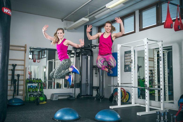 Kaksi naista jumppavaatteissaan hyppäämässä ilmaan bosupallojen päältä. Taustalla kuntosalin laitteita.