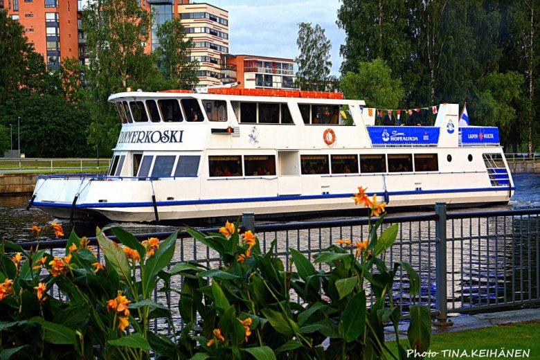 Hopealinjojen M/S Tammerkoski laiva purjehtii kohti Tampereen Laukontoria. Taustalla näkyvät kerrostaloja ja edessä kukkaistutuksia aidan vieressä.