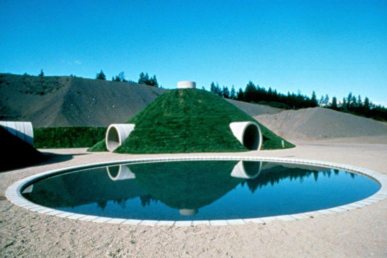 Maataideteos Yltä ja alta - Up and Under kuvattuna kesällä, jolloin taideteoksen nurmialueet ovat vihreitä ja etualalla olevassa vesiaiheessa on sinistä vettä. Taideteoksen ympärillä on harmaata hiekkaa ja taustalla näkyy sininen kesätaivas.