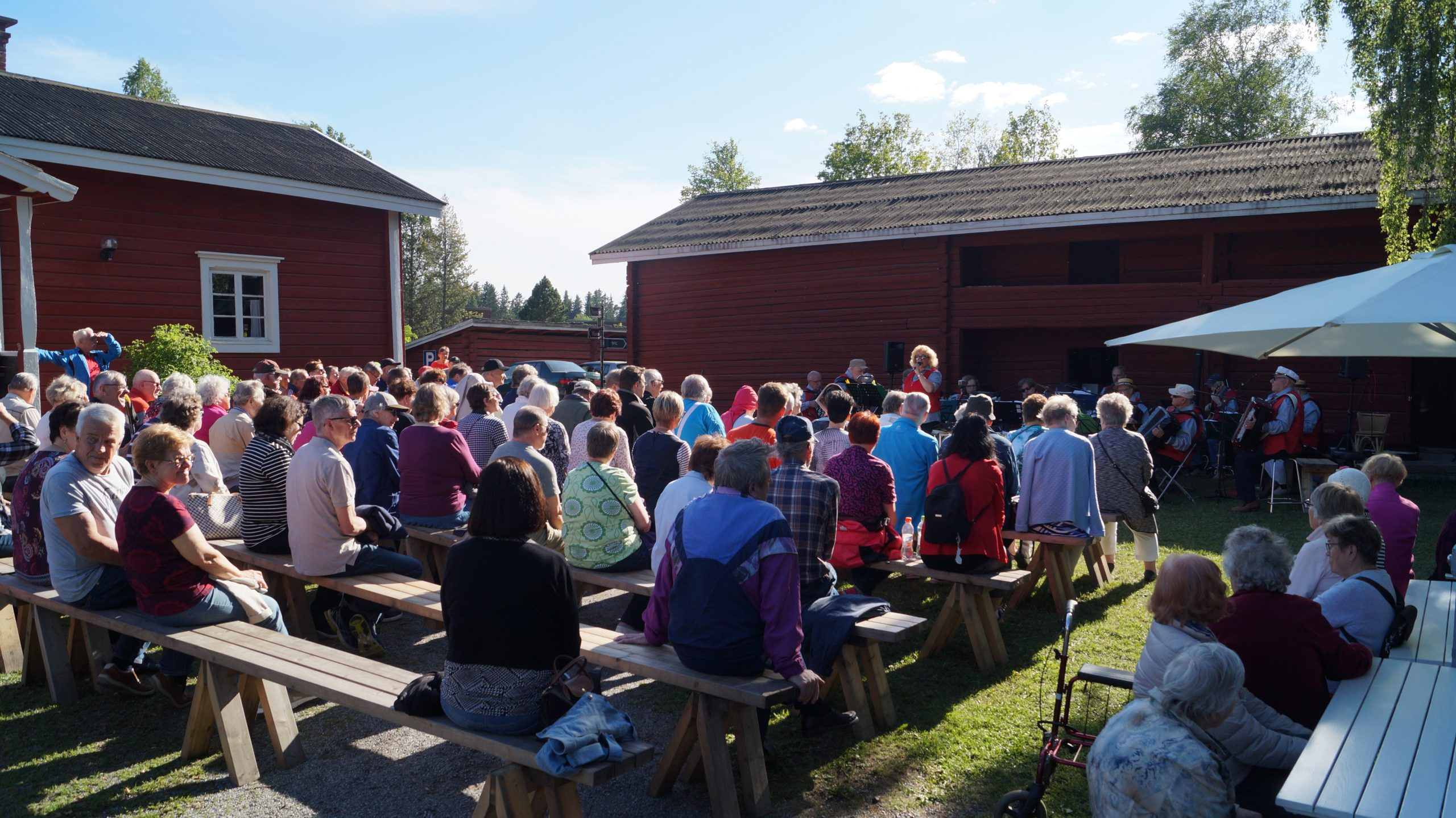 Hinttalan kotiseutumuseon sisäpihalle on kokoontunut runsaasti ihmisiä yhteislaulutilaisuuteen kesäiltana. Ihmiset istuvat pitkillä puupenkeillä ja edessä esiintyy Nokian Harmonikkakerho solisteineen.