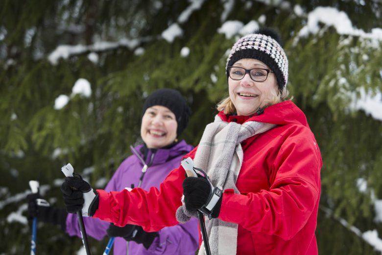 Kaksi naista hiihtää talvisessa maisemassa. Molemmat hymyilevät.