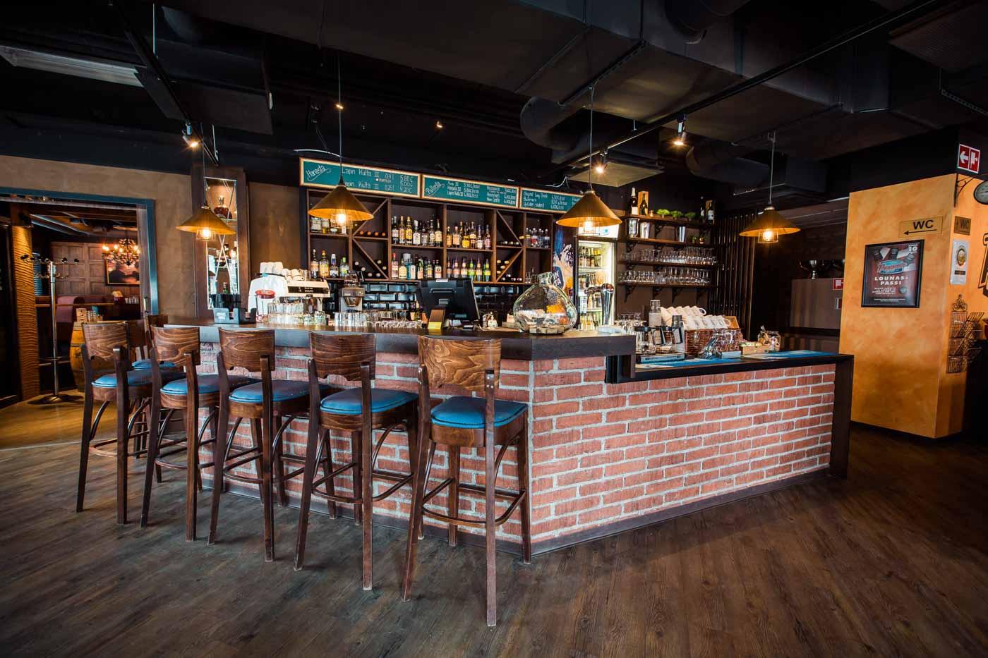 Pepper Bar & Restaurant -ravintolan punatiilinen baaritiski, jonka edessä korkeita puisia baarituoleja. Taustalla baaritarvikkeistoa ja pulloja hyllyllä.