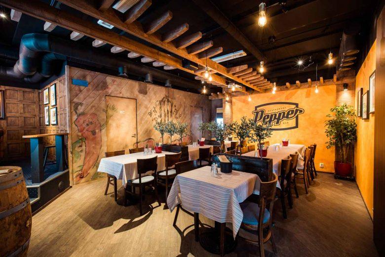 Pepper Bar & Restaurant -ravintolan sali, jossa ravintolanpöytiä ja -tuoleja kattauksineen.