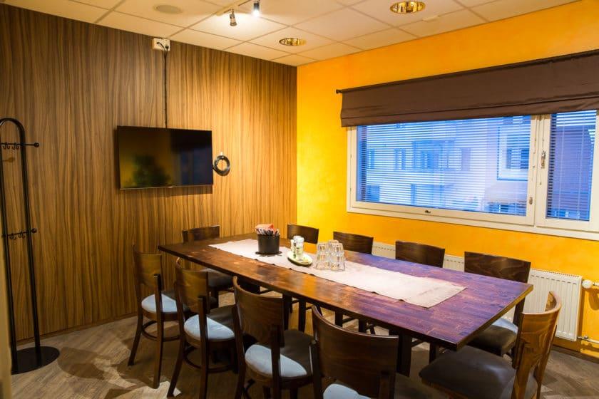 Pepper Bar & Restaurant -ravintolan neuvotteluhuone, jossa kymmenen hhengen pöytä tuoleineen ja seinällä plasmatv.