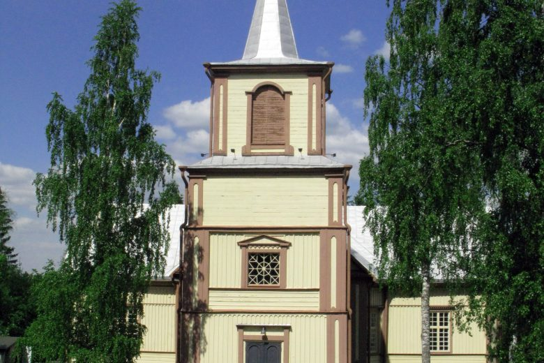 Suoniemen kirkko on vaaleaksi maalattu puukirkko, jossa on korkea kellotapuli ristillä.
