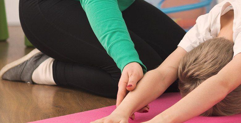 Lapsi venyttelee aikuisen ohjauksessa liikunta- ja fysioterapiapalvelu Vauhtiketun tiloissa.