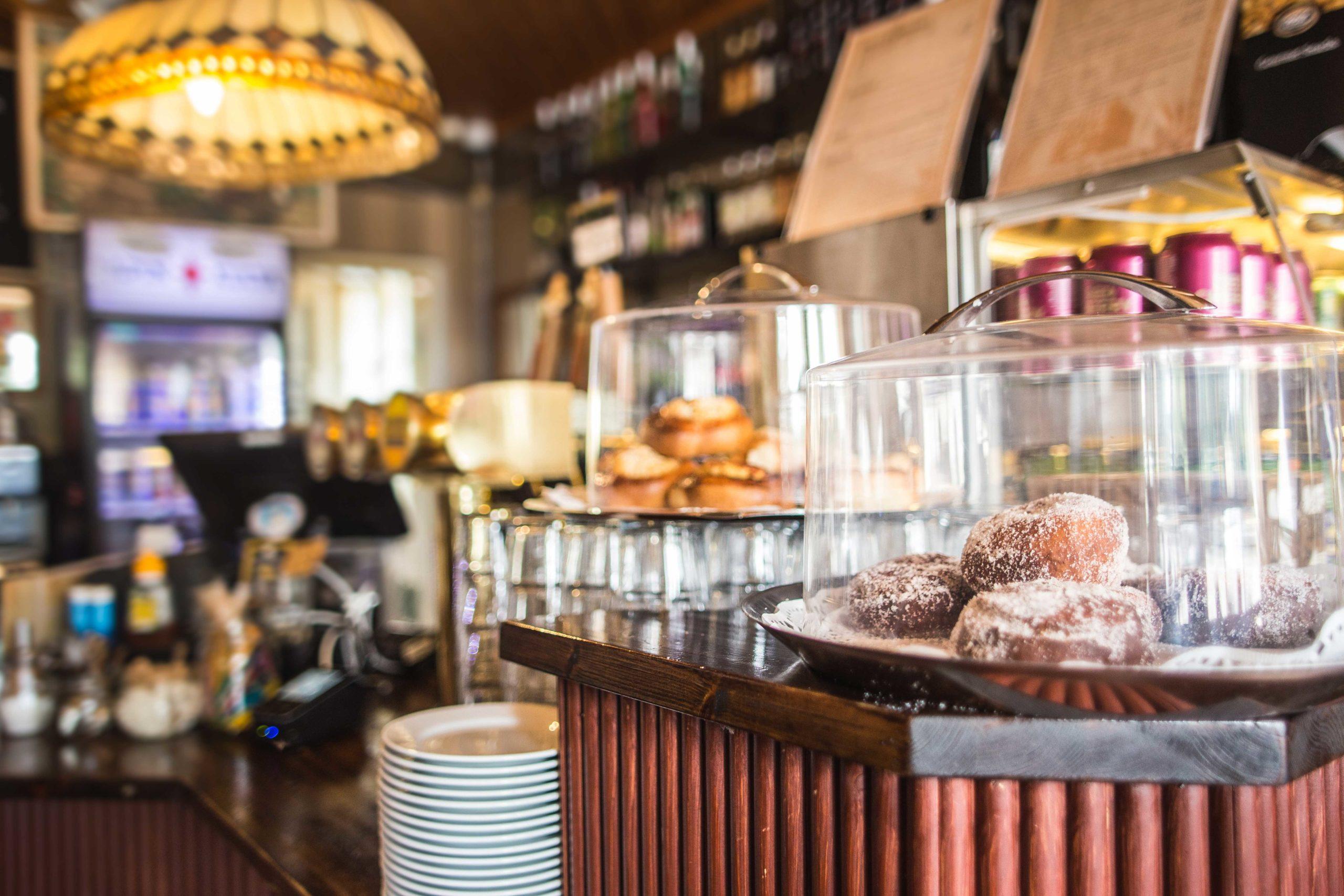 Siuron Koski-Baarin myyntitiski, jossa etualalla baarissa paistetuja munkkeja lasikuvun alla.