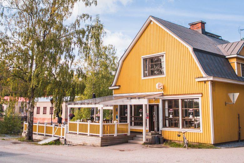 Siuron Koski-Baarin keltainen puurakennus, jonka edessä terassi ja taustalla näkyy Siuronkoski vanhoine voimalaitoksineen.