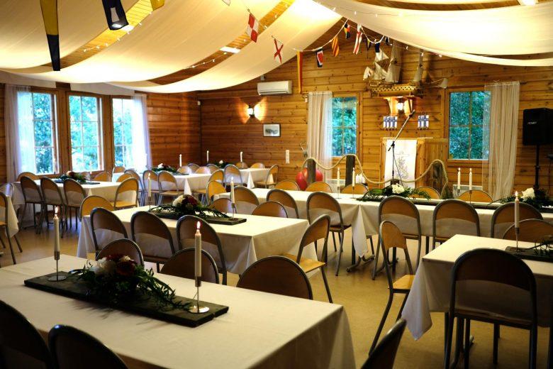 Juhla- ja kokoustila Ankkurin iso sali, jossa on runsaasti tilaa, pitkiä pöytiä ja tuoleja. Salin pöydät on katettu juhlavasti valkoisilla pöytäliinoilla, kukka-asetelmilla ja kynttilöillä.