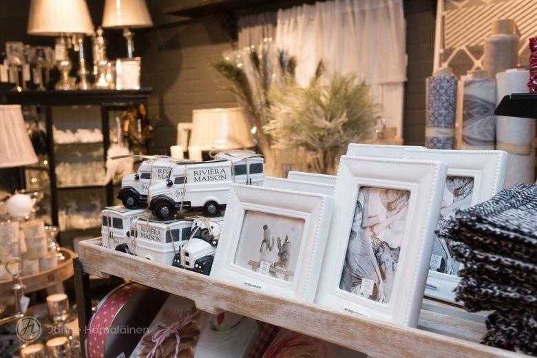 Sisustusliike Eveliinan Talon kauniita sisutusesineitä esillä myymälässä. Hyllyssä mm. valkoisia puuvalokuvakehyksiä.