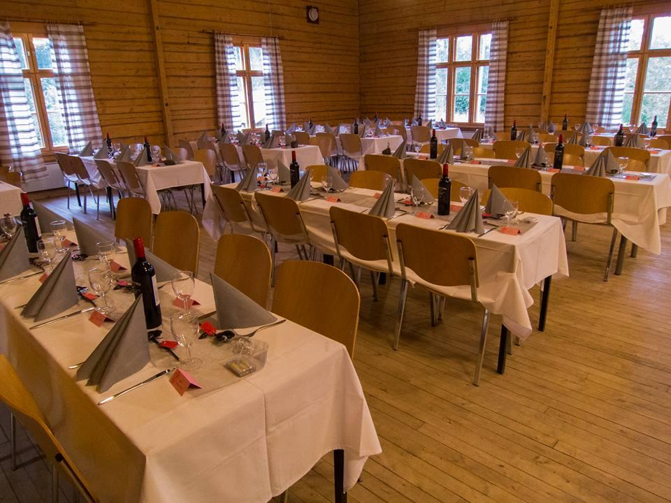 Tottijärven Jukolan suuri sali, johon katettuna juhlakattaus pitkille pöydille. Pöydillä valkoiset pöytäliinat, aterimet, lautasliinat sekä viinipullot.