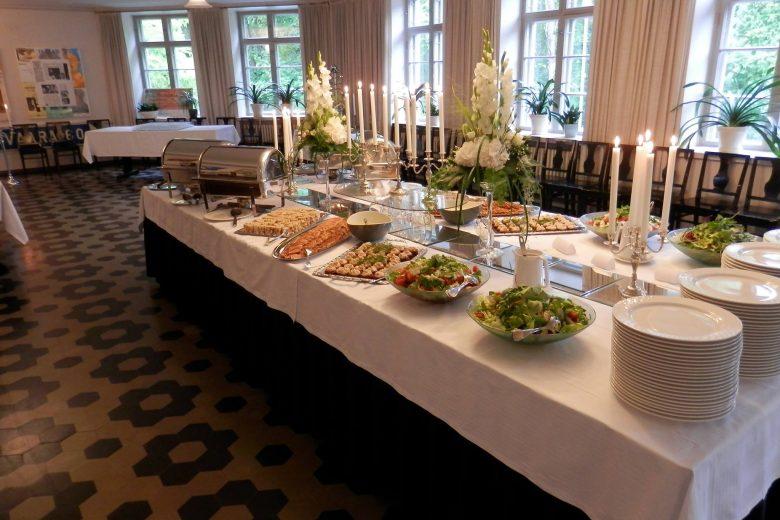 Lounas-Cateringpalvelu Kahden Kölvin kattama pitopöytä Nokian Kerholan vanhoihin tiloihin. Buffetpöydässä on esillä salaatteja, kala- ja liha-alkupaloja sekä lämpimiä ruokia teräksisissä astioissa.