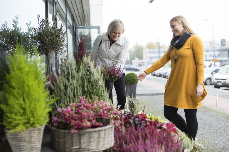 Kukkaputiikin myyjä asiakkaan kanssa liikkeen edessä