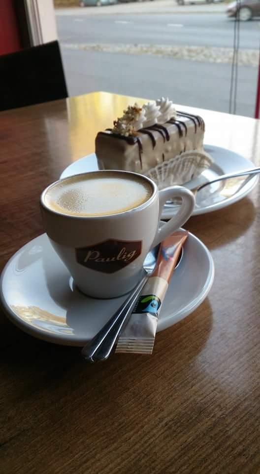 Konditoria Lehtosen valmistama erikoiskahvi maitovaahdolla sekä kinuski-suklaaleivos, jossa on päällä kermavaahtoa.