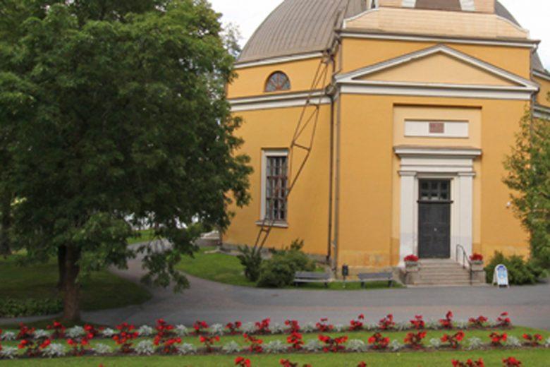 Nokian keltainen kivikirkko, jonka ympärillä vihreää nurmikkoa ja puita sekä sankarihautoja, joiden päällä punaisia kukkaistutuksia.