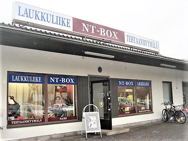NT-Box-laukkumyymälä sijaitsee Alinenkadulla. Myymälässä on isot lasi-ikkunat, joissa on esillä myymälän laukkuvalikoimaa.