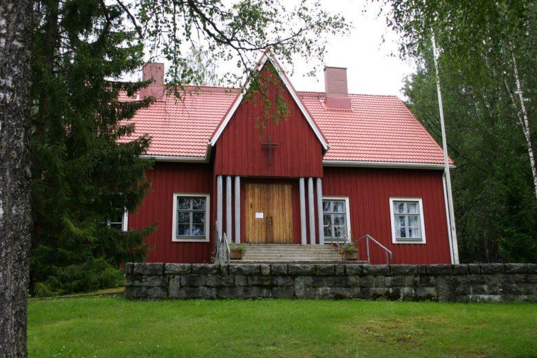 Pinsiön punainen puukirkko, jossa valkoiset ikkunanpielet ja oven yläpuolella risti. Kirkko sijaitsee metsäisessä ympristössä.