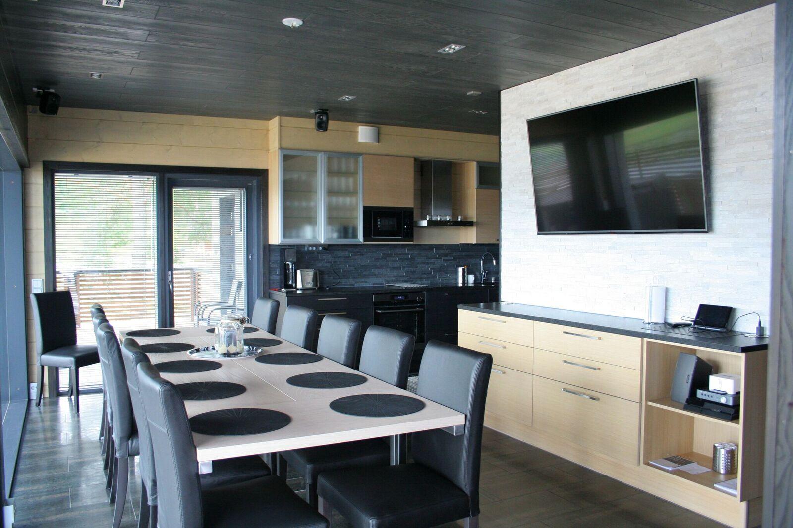 Ellivuoren Ranta Villan keittiö, jossa laadukas keittiö, kymmenen hengen iso ruokapöytä ja plasma-tv.