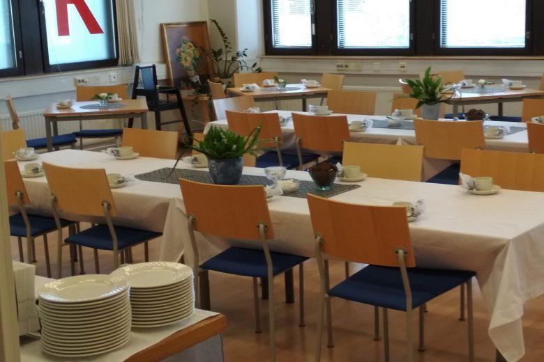 Suomen Punaisen Ristin Nokian osaston juhlatila, jossa pöytiä ja tuoleja juhlakattauksessa. Pöydillä valkoiset pöytäliinat ja kukka-asetelmat. Kattoon on ripustettu paperikennopalloja ja serpentiiniä.