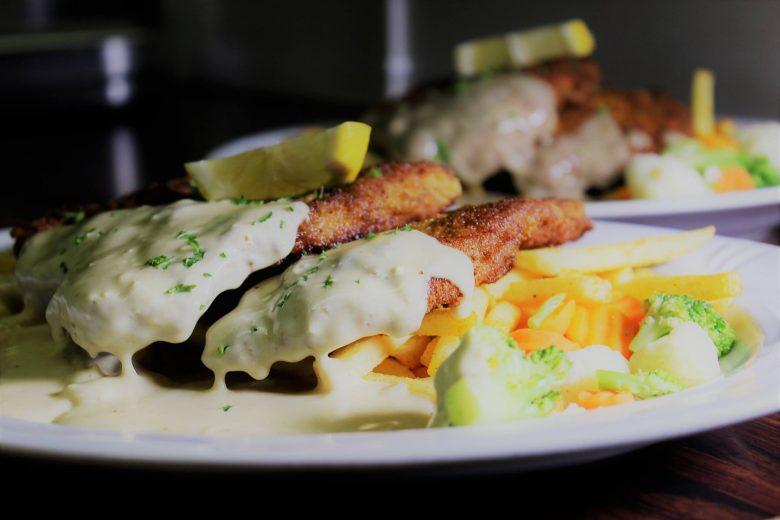 Steaktime-ravintolan annos, jossa paneroituja pihvejä kastikkeella sekä runsaasti erilaisia höyrytettyjä vihanneksia.