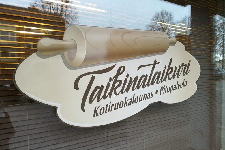 Taikunataikureiden ravintolan ikkuna, jossa Taikinataikureiden logo. Logossa yrityksen nimi ja kaulimen kuva.