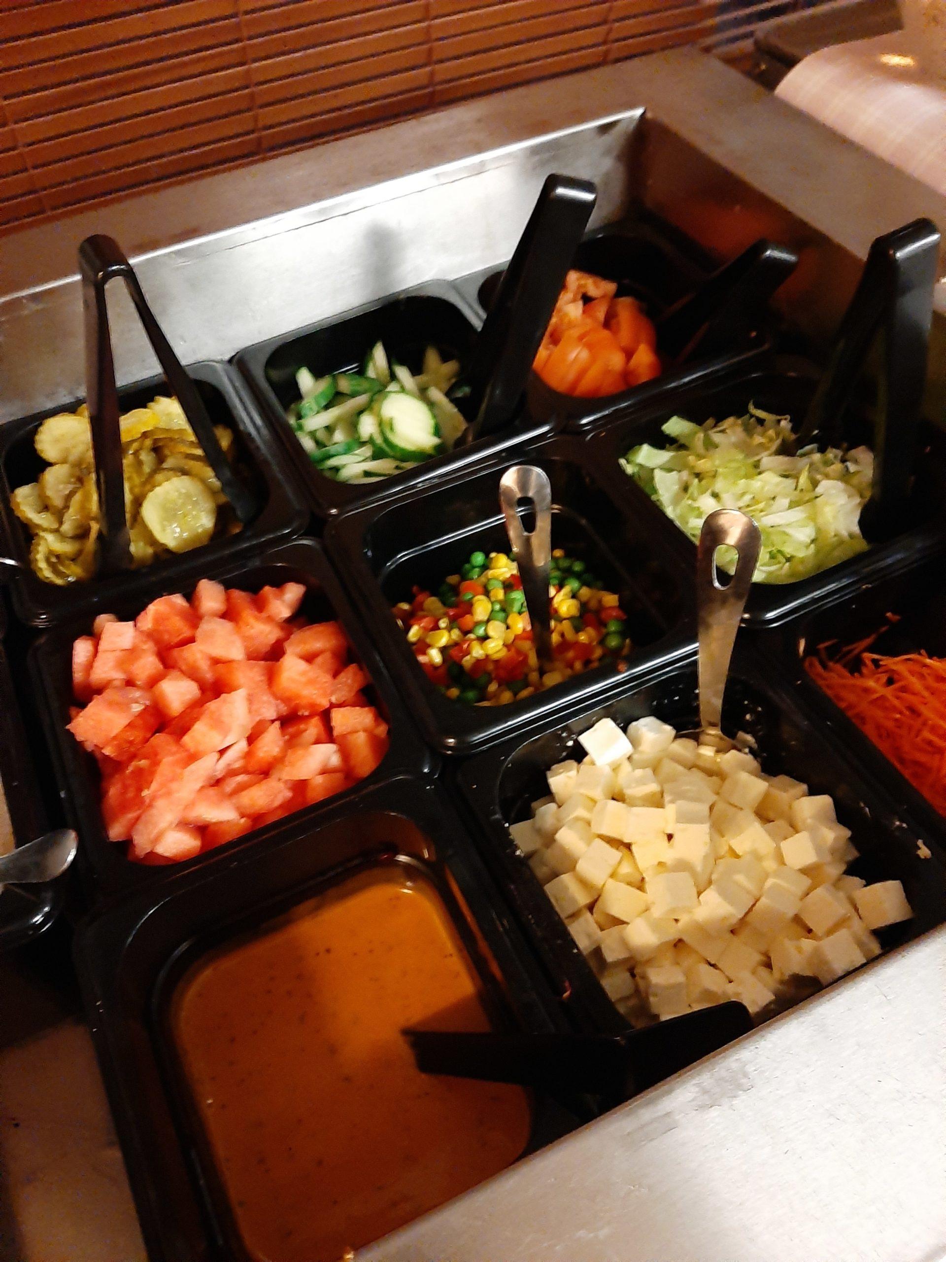 Taikinataikureiden ravintolan salaattipöytä, jossa tarjolla mm. salaattia, kurkkua, vesimelonia ja fetajuustokuutioita.