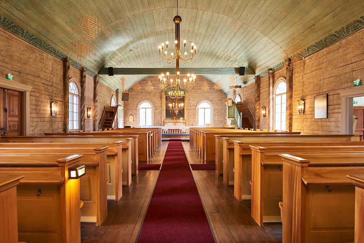 Tottijärven kirkko on sisältä puinen. Kirkon keskiosaa halkoo tummanpunainen matto ja sen molemmilla puolilla on puunvärisiä kirkonpenkkejä.