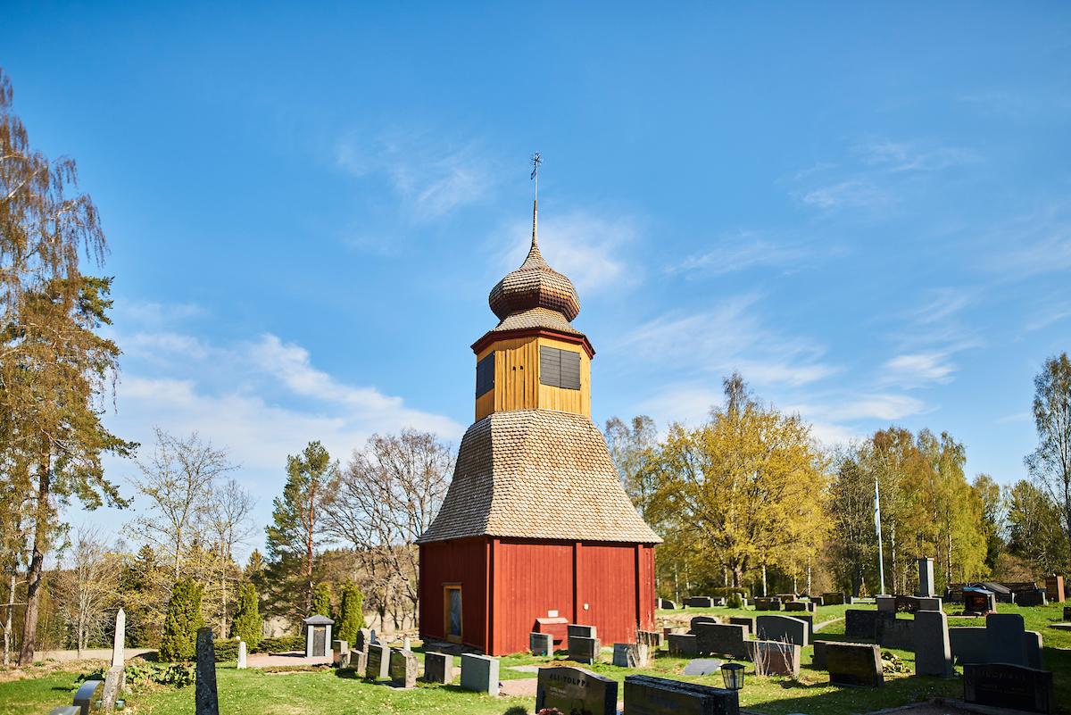 Tottijärven kirkon kellotapulia ympäröi hautausmaa.