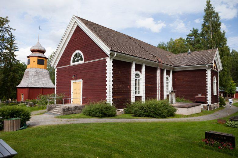 Tottijärven puinen kirkko, joka on maalattu punamultamaalilla. Kirkon ikkunanpielet ja ovenkarmit ovat maalattu valkoisiksi ja pääovi keltaiseksi. Kirkon edessä on nurmikenttää, hiekkatie ja hautoja.