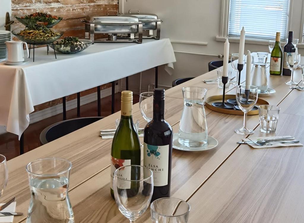 Alastalon kartanon juhlatilan pöydälle on katettu juhlakattaus ja pöydällä on myös kynttilöitä ja viinipulloja.