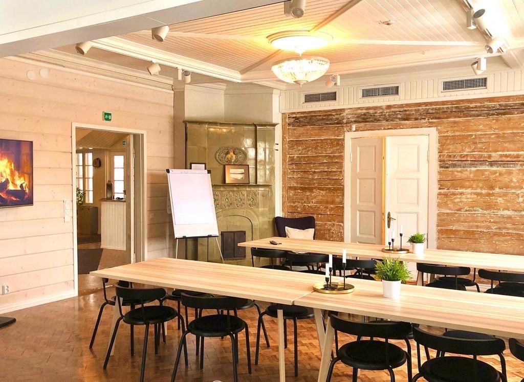 Alastalon kartanon remontoitu kokoustila, jossa on pitkät vaaleat pupöydät, mustat tuolit ja seinissä tiiliverhoilu.