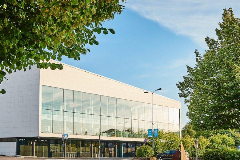 Valkoinen kirjasto- ja kulttuuritalo Virran rakennus, joka sijaitsee Nokian keskustassa. Talon edessä on vihreitä puita ja taivas kesäisen sininen.
