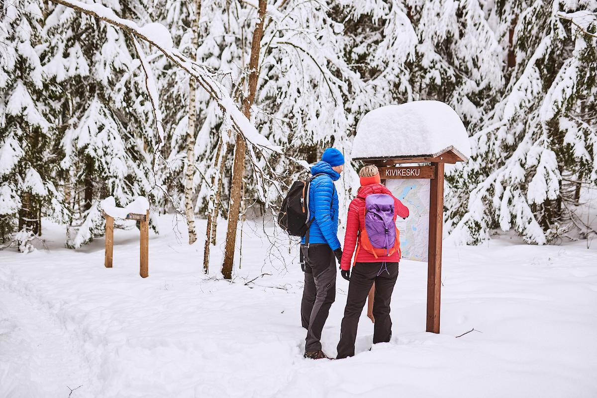 Värikkäisiin ulkoiluvaatteisiin pukeutuneet nainen ja mies tutkivat Kivikeskun opaskylttiä talvisessa metsässä.