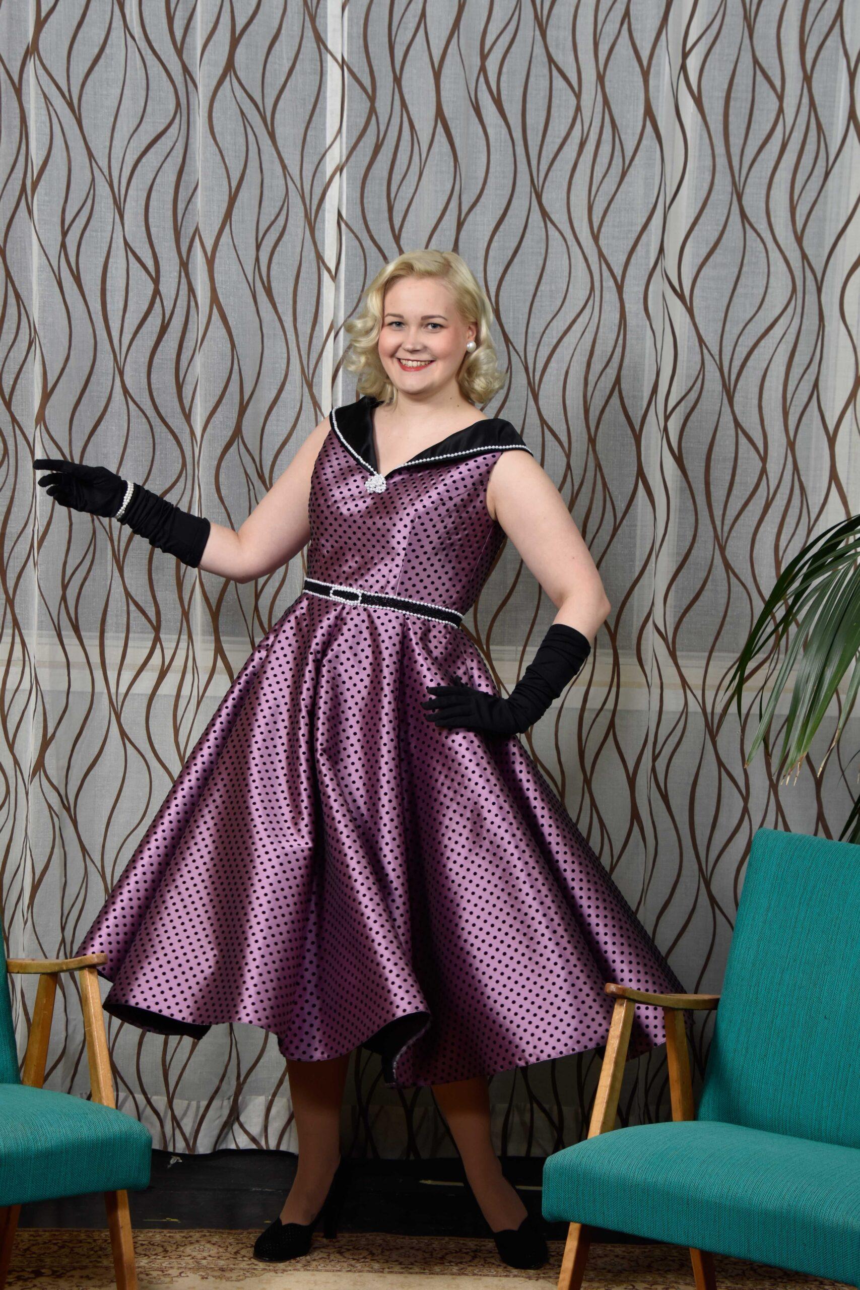 Nuori nainen hymyilee kiiltävässä violetissa juhlamekossaan.