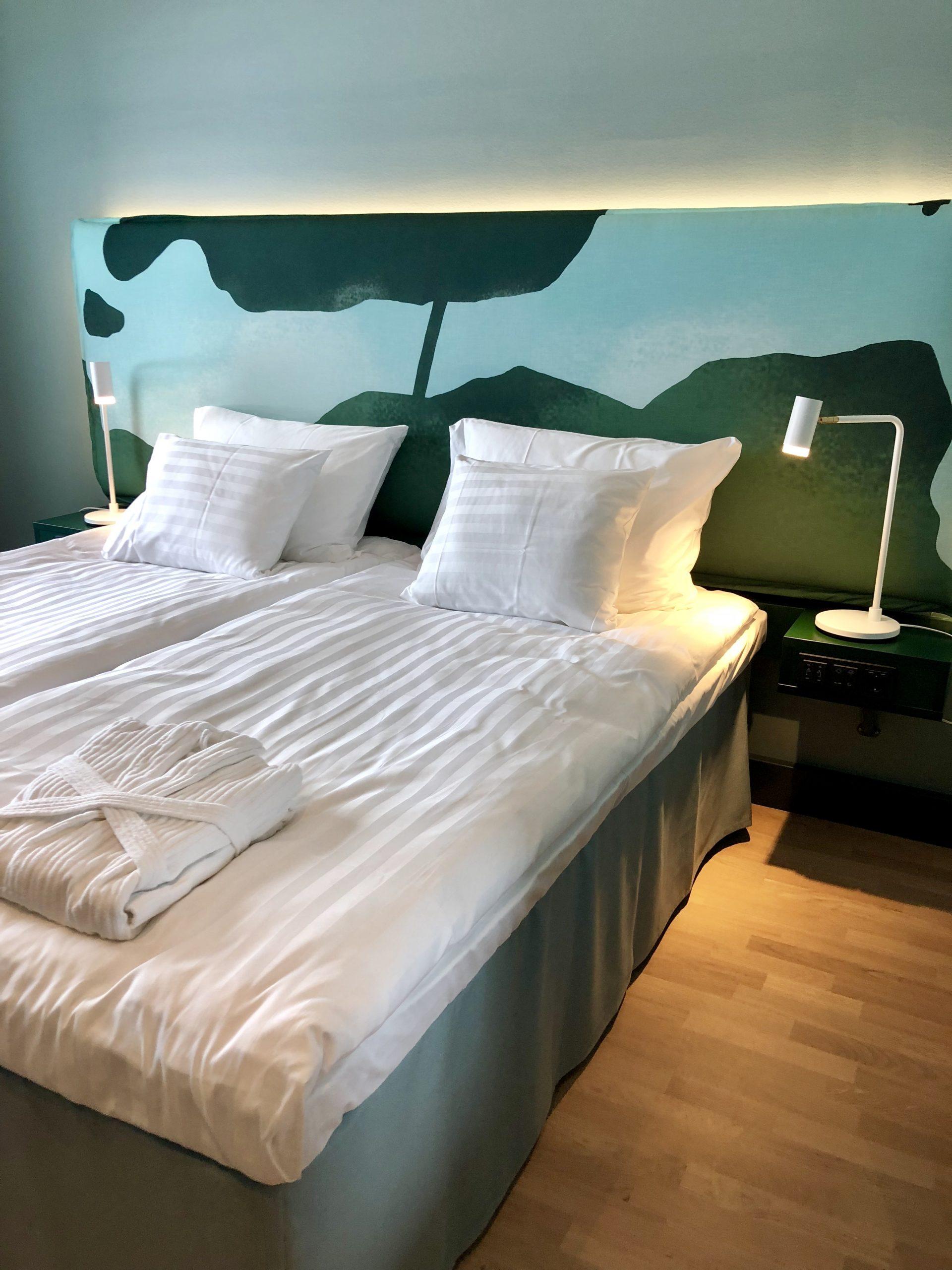 Scandic Eden Nokian uudistettu hotellihuone, jossa pedattuna iso parisänky valkoisilla lakanoilla.
