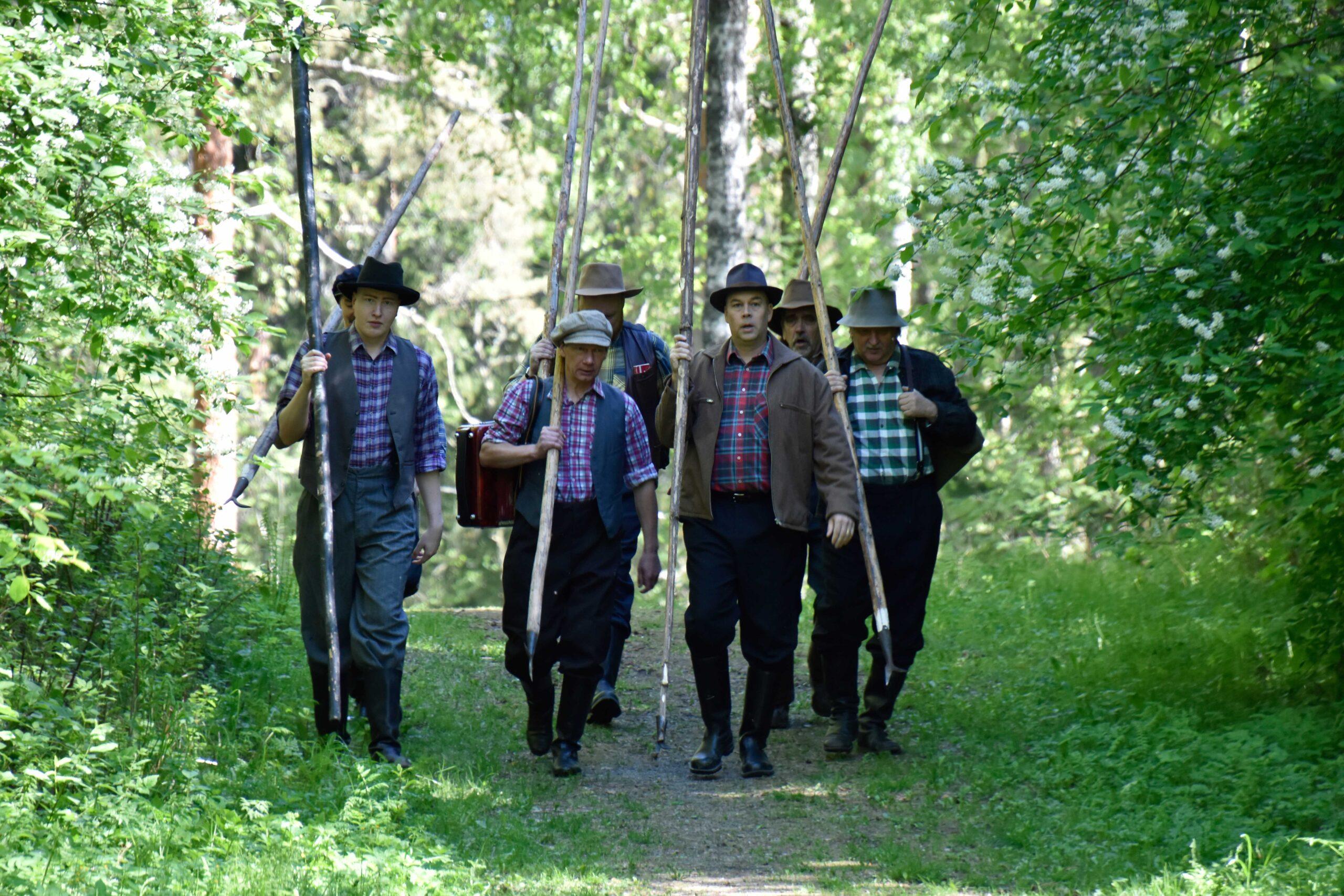 Kuuden miehen tukkilaisjoukko kävelemässä metsän siimeksessä.