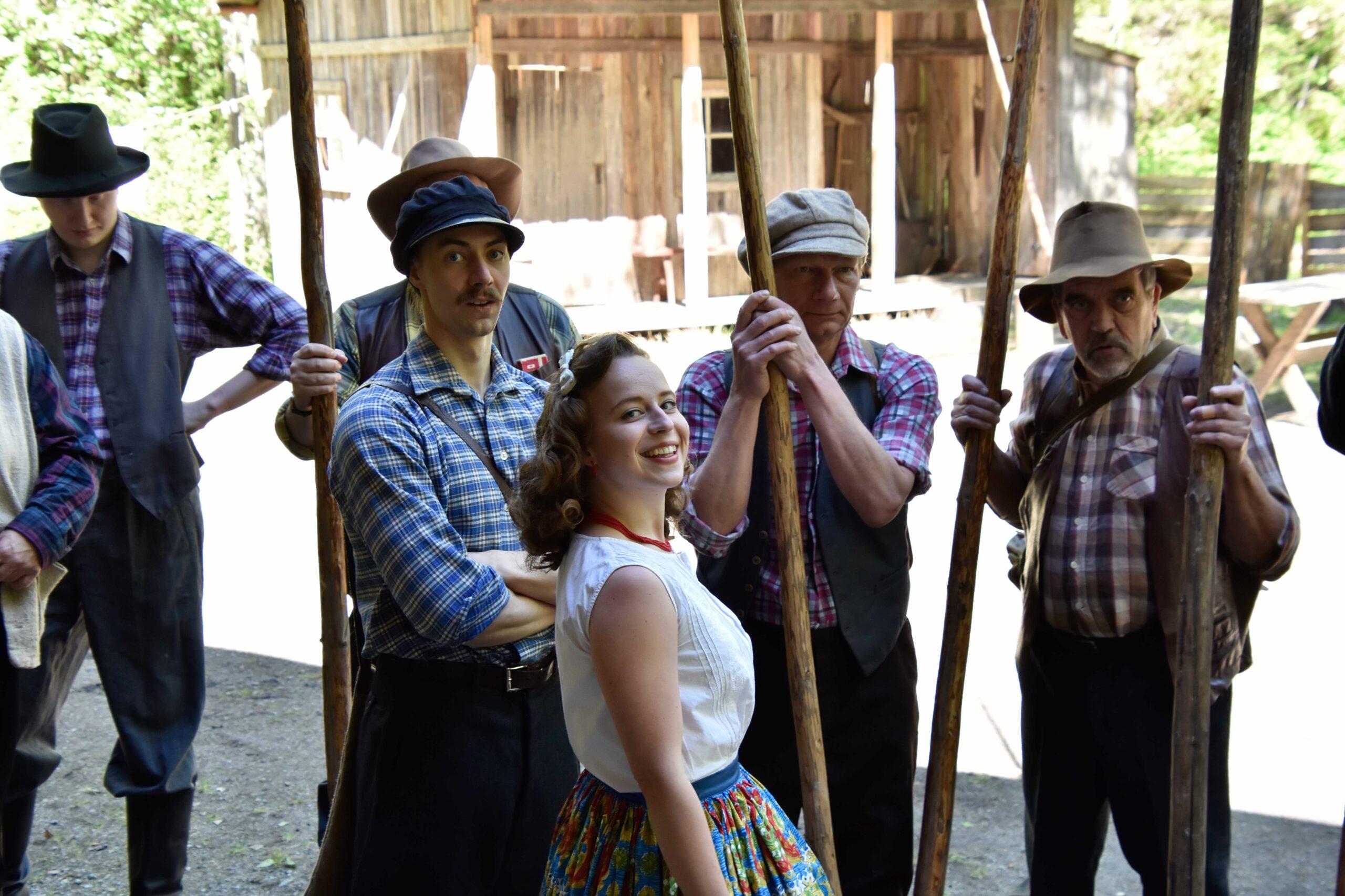 Tukkilaismiehet ja nainen hymyilemässä kesäteatterin näytelmässä.