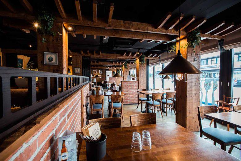Pepper Bar & Restaurant -ravintolan sali, jossa ravintolanpöytiä ja -tuoleja kattauksineen sekä isot ikkunat Välikadulle.